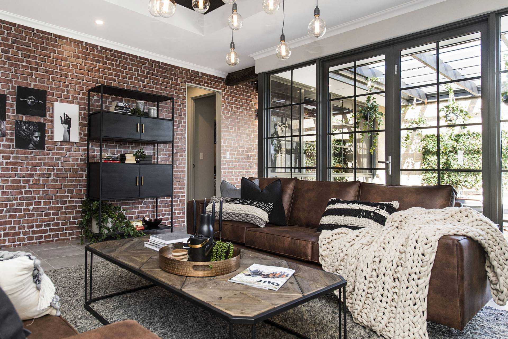 tribeca home with raw face brick walls tiled floor and leather couch