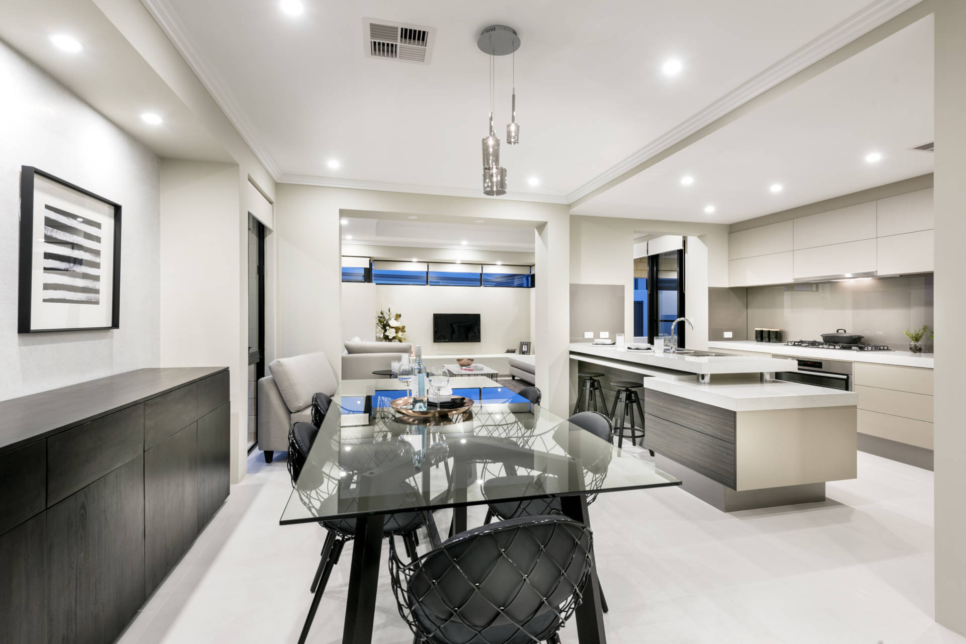 Dining room with high-gloss white kitchentop and glass dining table with charcoal modern chairs and open living room