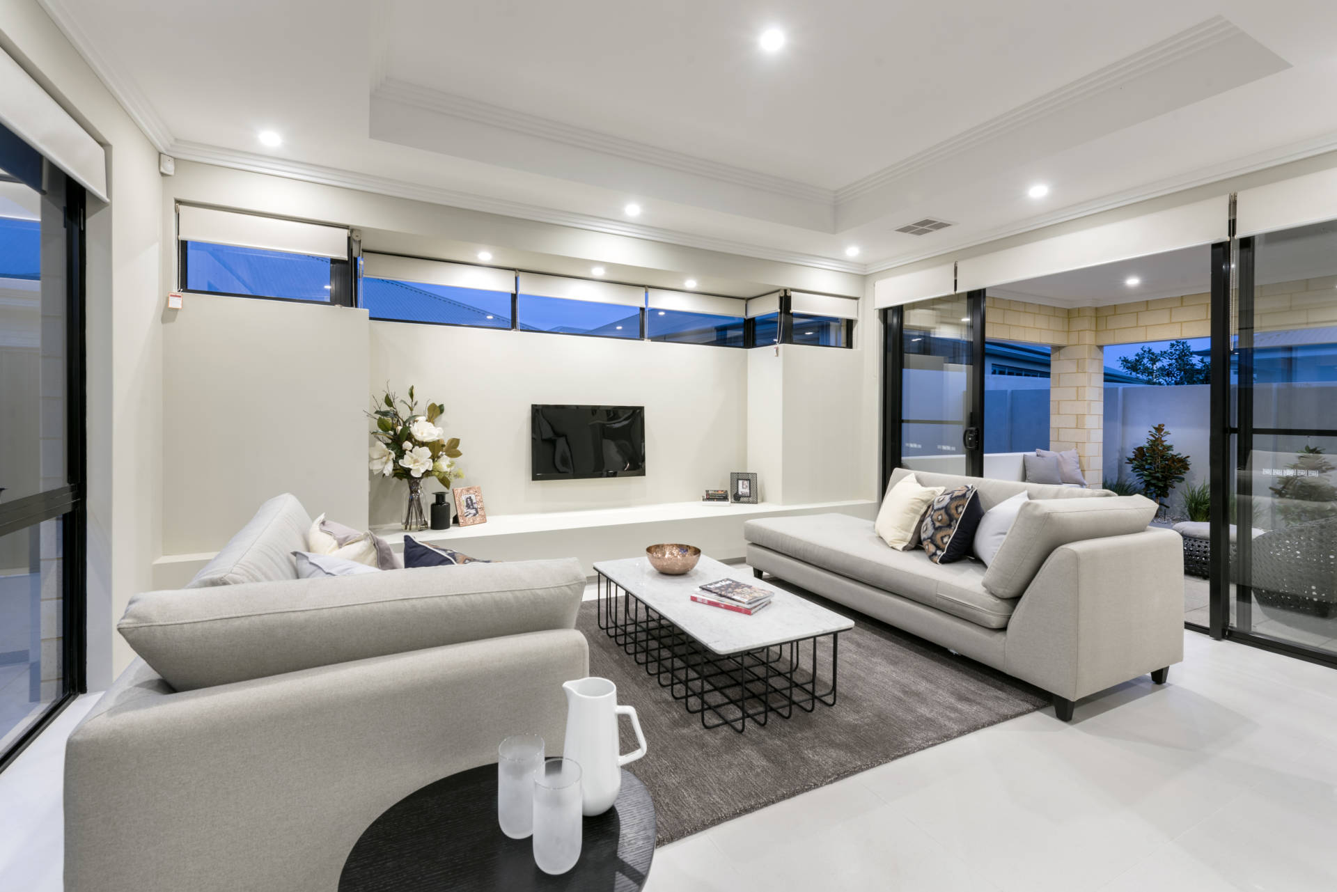 Modern spacious living room with light grey and egg shell decor leading into a patio through large sliding doors