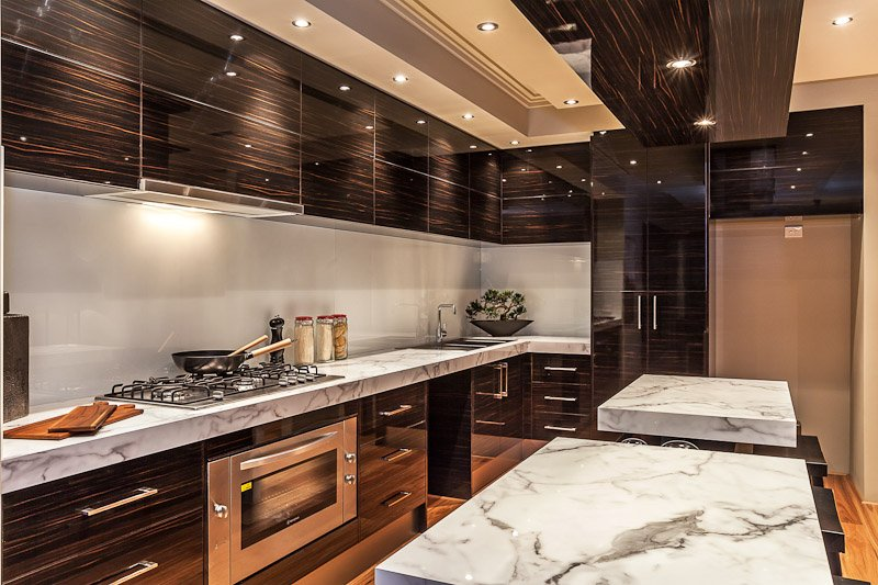 Luxury home interior that boasts a eautiful kitchen with custom cabinets gas stove top and endless marble topped island and planked hardwood floor.