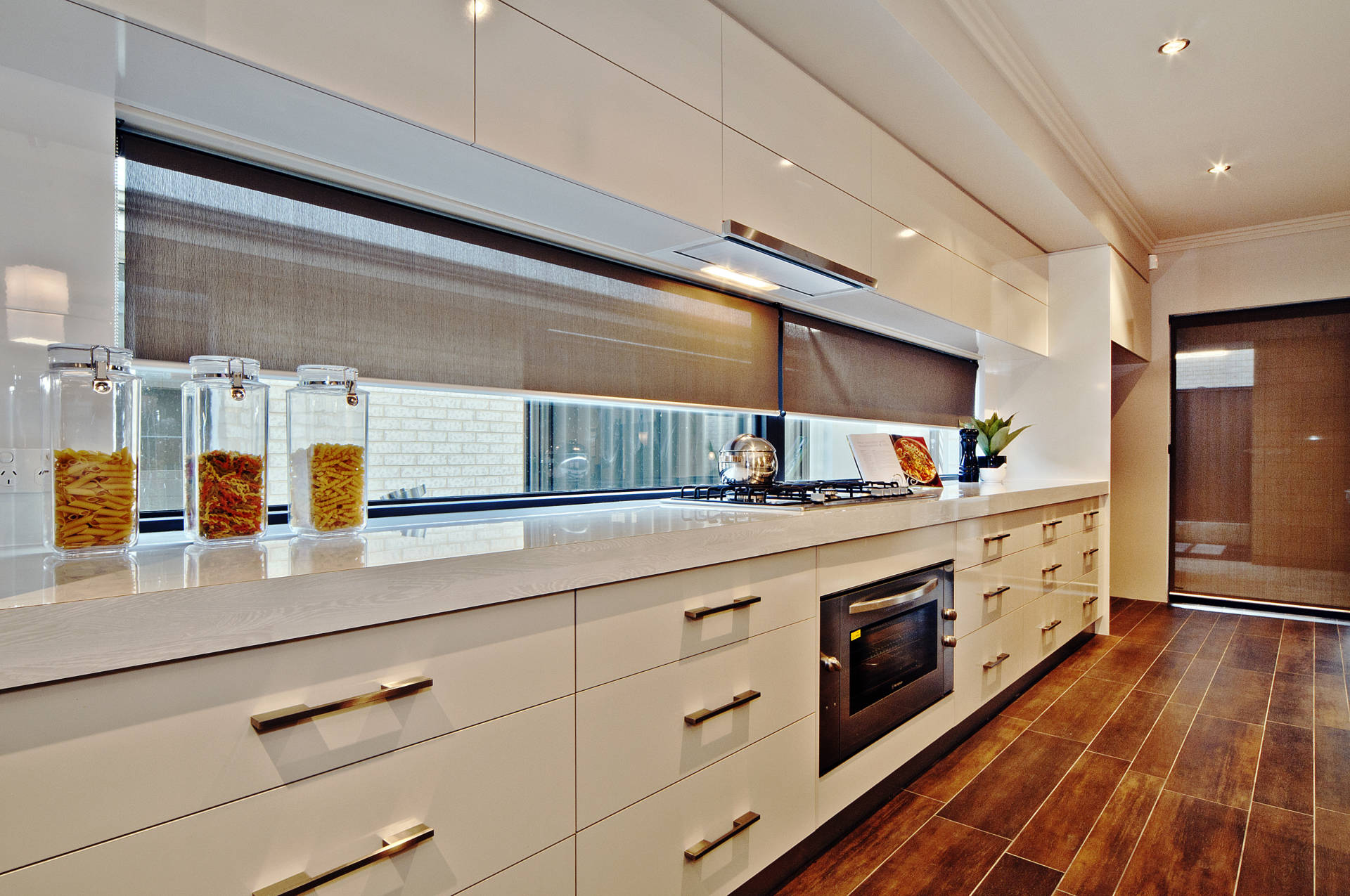 Modern kitchen interior with white cabinets, wooden tiled floor gas cooker and elongated window