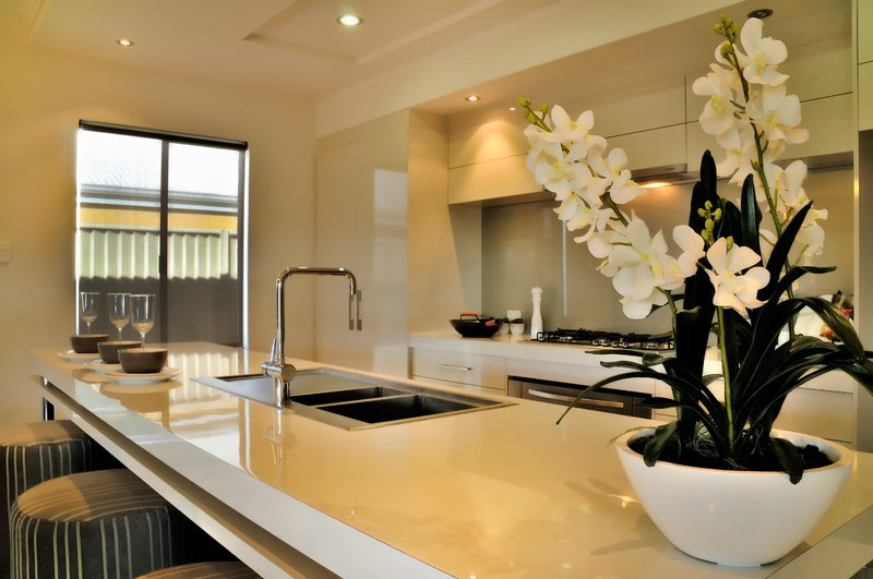 Open plan kitchen with living room in modern house with white marble countertop and warm downlights